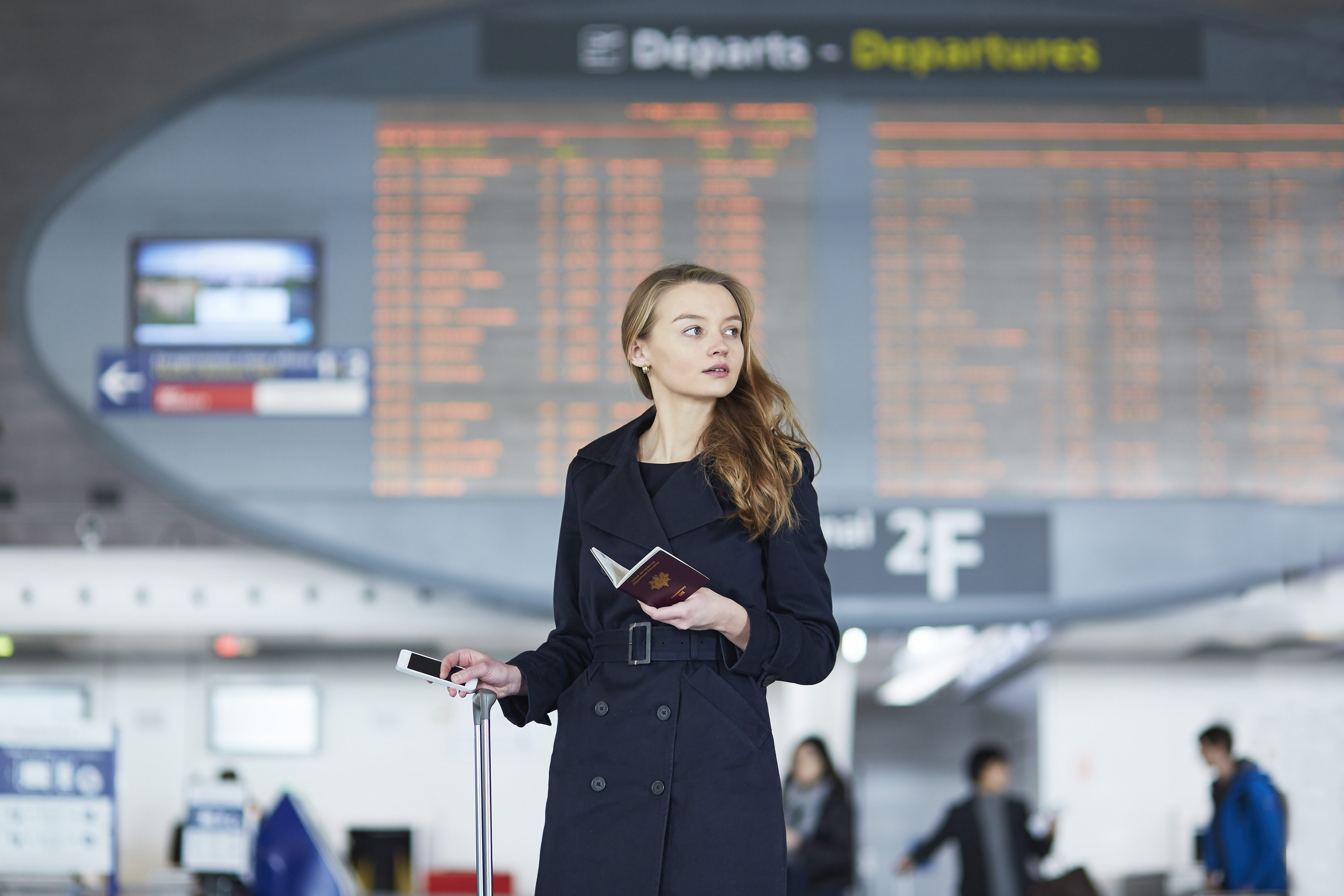 Young woman in international airport near the flight information board, looking in her passport